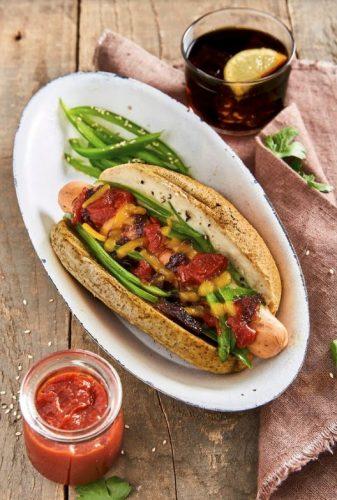 Gourmethotdogs med sauce af cannellinibønner, grøn peberfrugt, karamelliseret rødløg, revet ost og ketchup