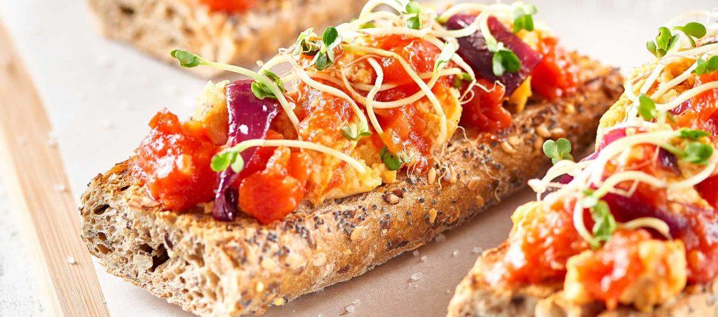 Mørkt brød ved rørt egg og tomat
