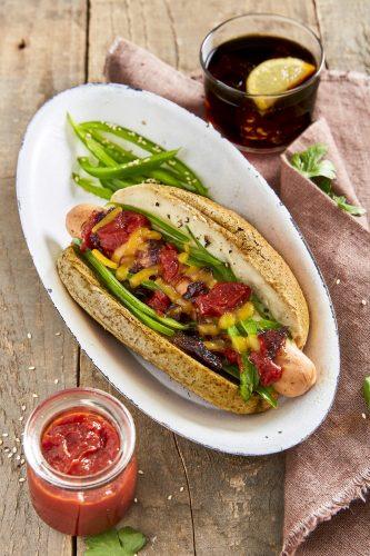 Gourmethotdogs med saus med cannellinibønner, grønn paprika, karamellisert rødløk, revet ost og ketchup