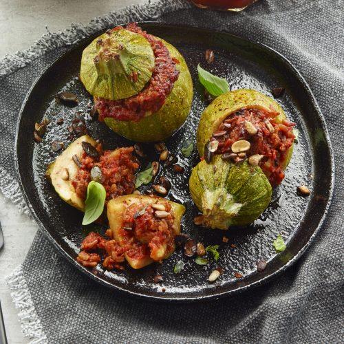 Rund fylld zucchini med tomatsås med chilipeppar, vildris och rostade frön