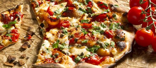 Pizza garnie aux tomates, au fromage de chèvre, aux poivrons, aux câpres et aux herbes
