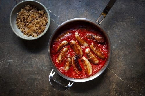 Lamb sausages in tomato sauce with bacon sauerkraut