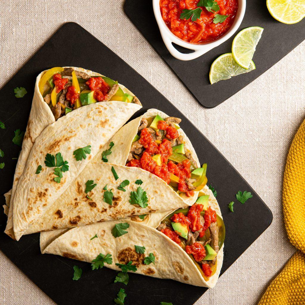 Fajitas with beef, tomatoes, avocado and lime