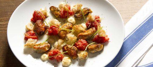 Smażone małże podane z pomidorami, chrzanem i kolendrą