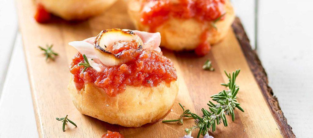 Pizzette con polpa fine di pomodoro, cipolle grigliate e pancetta dolce