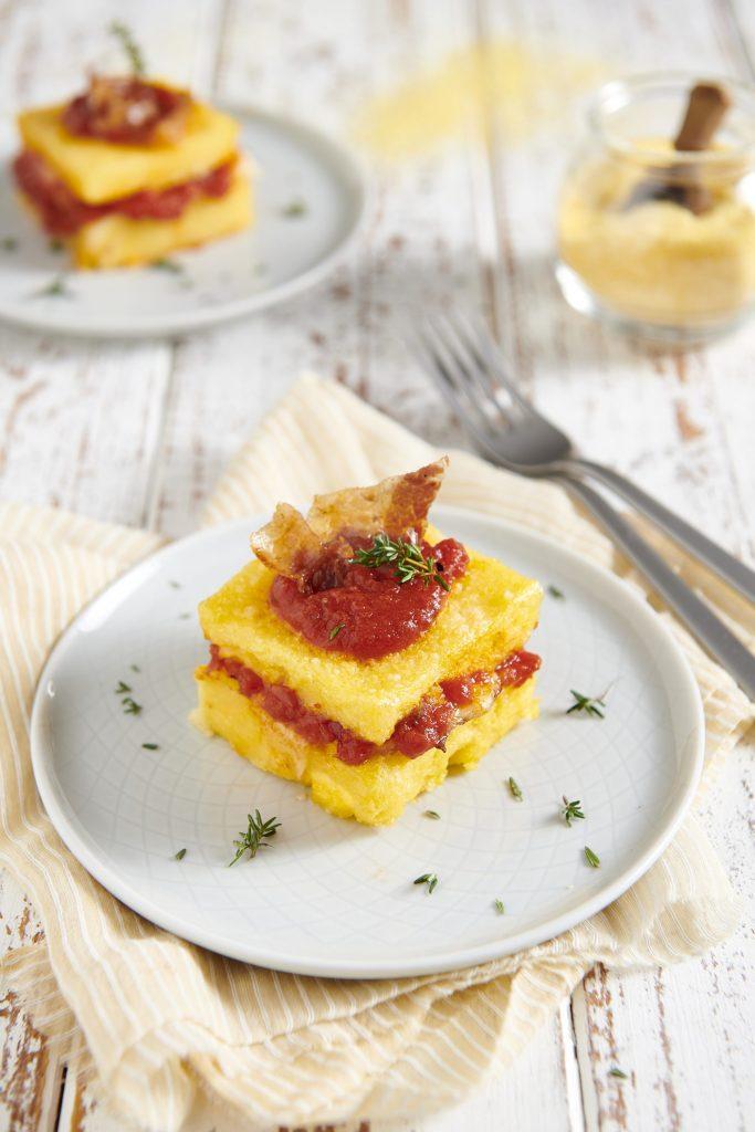 Polenta concia con formaggio, speck e salsa di pomodoro