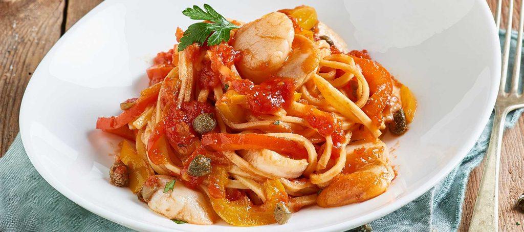 Tagliolini-pastaa paprikoiden, tomaatin, kapristen ja kampasimpukoiden kera