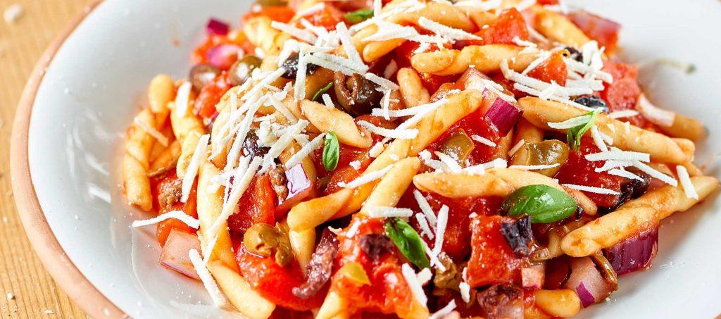 Strozzapreti-pastaa, ricotta salata-juustoa ja marinoituja kuorittuja tomaatteja