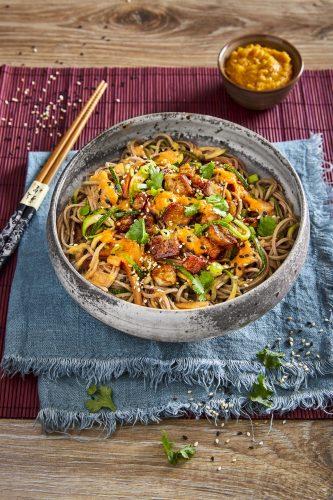 Thaimaalainen vihanneswokki nuudelien, kesäkurpitsan, salaattisipulin, mustien seesaminsiementen, tofun ja oranssin peston kera